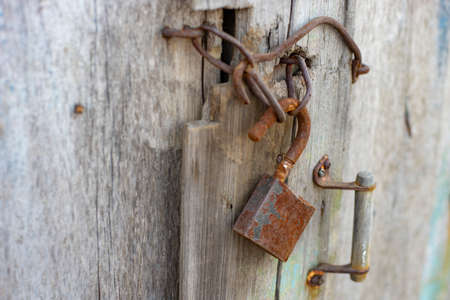 Old wooden door with rusty handle, hook and lock. 스톡 콘텐츠