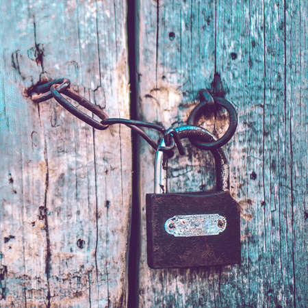 Old pale blue wooden door with a lock and a chain. Boho style Stock Photo