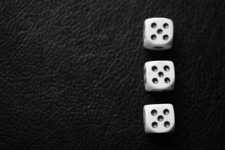 Three dice with fives on a black leather table. Bw photo. Top view. Copy space