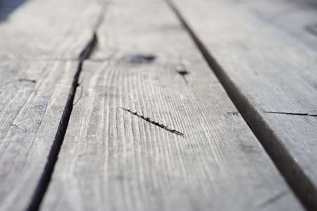 background old gray wooden floor made of planks and deep holes. Imagens