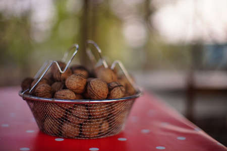Mesh bowl full of walnuts on a red tablecloth with white dots.