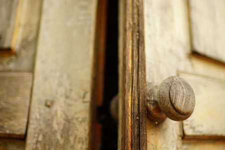 old brown shabby wooden door with a round knob