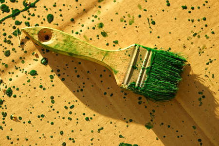 old brush stained with green paint on the dirty brown paper sheet.