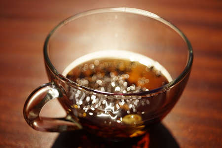 Glass cup with black tea on the brown wooden table. Closeup view. Stock Photo