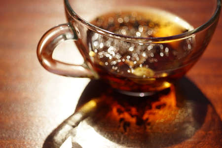 Glass cup with black tea on the sunny brown table. Closeup view with amazing light and shadow. Stock Photo
