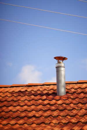 Red tile roof with galvanized chimney chimney against blue sky. Standard-Bild