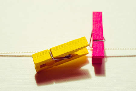 Two wooden clothespins yellow and pink on a white table.
