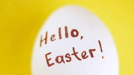 White chicken egg with black inscription hello easter on a yellow background Zdjęcie Seryjne
