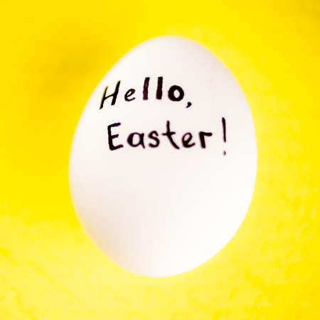 White chicken egg with black inscription hello easter on a yellow background