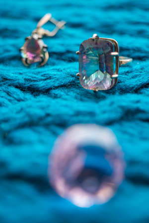 Silver ring with a large stone mystical topaz on a knitted blue table