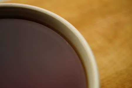 Closeup ceramic cup with black ceylon tea on wooden board.