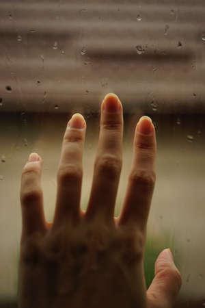 Hand touches a window in rain drops.