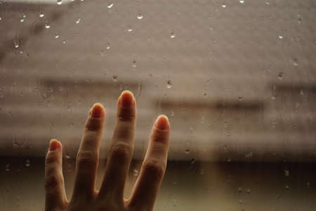 Hand touches a window with rain drops. Roof background in blur.