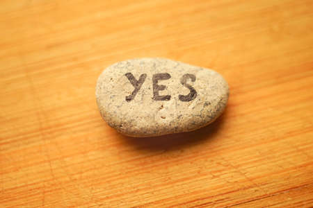 Pebble stone with the text yes on light yellow wooden table. Фото со стока