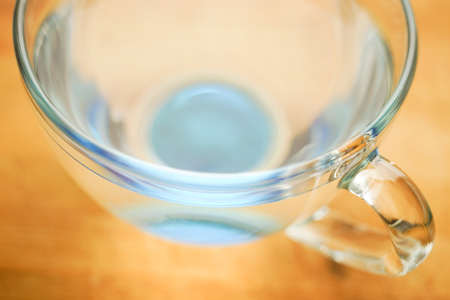 Full blue transparent glass of water on a wooden table