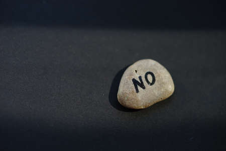 Pebble stone with text NO on black table.