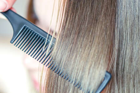 The process of combining a fine black comb for medium brown hair with a silver shine. Фото со стока