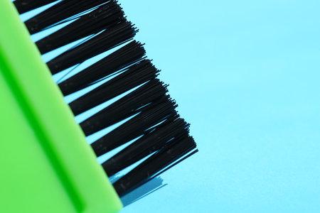 new green hair dye brush on blue table.