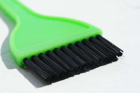 new green hair dye brush on white table. Фото со стока
