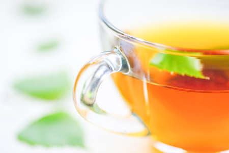 Herbal tea in a glass cup with green leaf. Leaves on a white table around a mug with a drink. Фото со стока