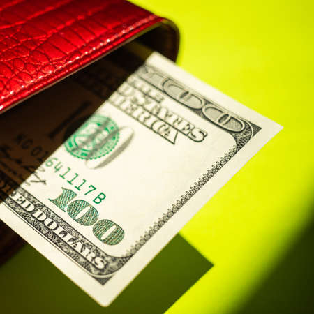 Hundred dollar bill sticking out of a red purse over sunny green table with strong shadows. Фото со стока