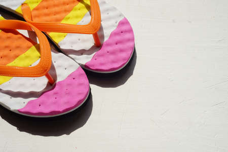 Colored beach flip flops on a striped towel. Positive summer still life. View from above. Copy space