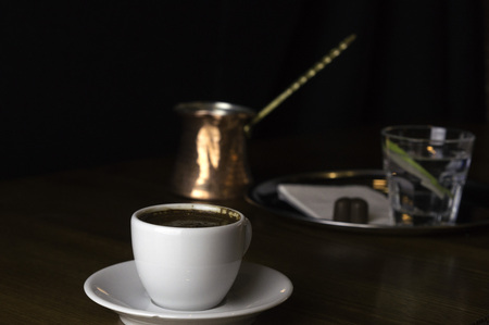 a glass of coffee with coffee pot and chocolate beside a coffee with milk in a white cup placed on a brown table