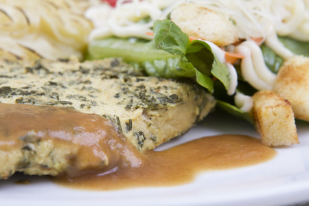 meat alternatives: Pork steak served with mashed potatoes and salad.