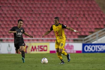 premier league: BANGKOKTHAILAND:JUNE 2015:FWAddison Alves No.20 Osotspa F.C yellow.vs MFSiwakorn No.24 Bangkok Glass F.C.blackat Rajamangala National StadiuminThai Premier League on 27 june2015Bangkok Thailand. Editorial
