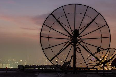 antena parabolica: Antena parabólica en el crepúsculo edificio.