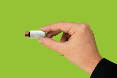 Flash memory on hand with isolated green background