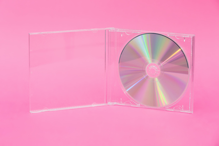 DVD in transparent box on pink background. Front view