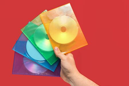Several boxes of CD on hand with red background. Front view Stock Photo