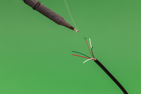 Soldering a copper wire on green background. Front view