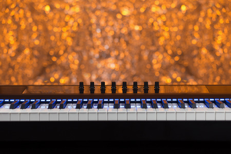 Midi electric piano with blue lights. On orange background out of focus