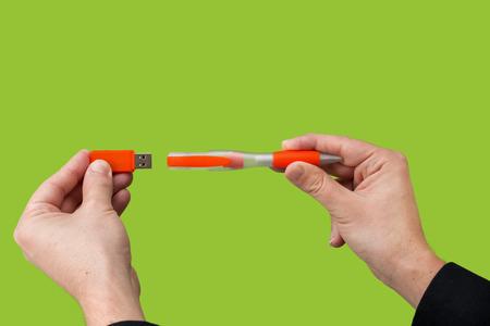 USB orange flash drive in hand. Green background