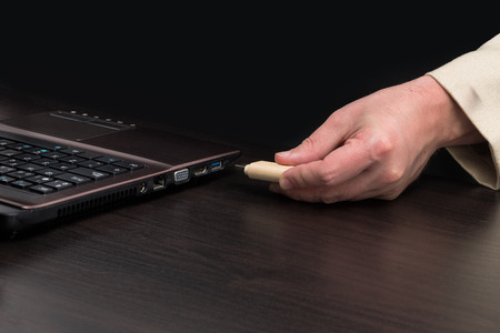 USB flash memory by hand connecting to a laptop. Front view
