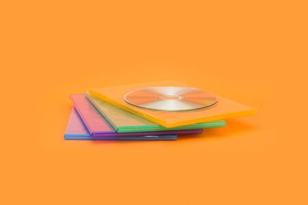 Several DVD  CD boxes on orange background. Front view