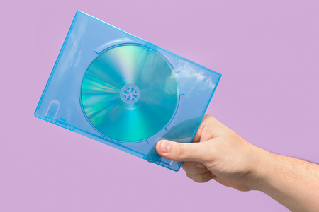 DVD  CD box in hand with violet background. Front view Stock Photo