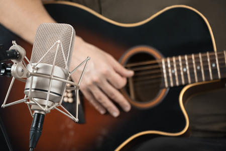Microphone recording an acoustic guitar played by hand. Front view