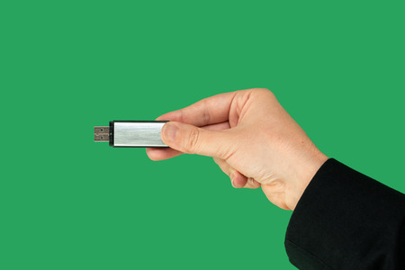 Metal pen drive on hand with isolated green background. Front view Stock Photo