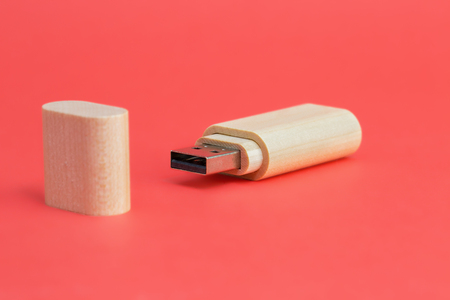 Wood USB flash drive on a red background. Front view Stock Photo