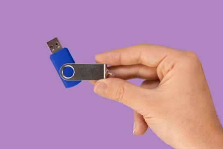 Blue USB flash memory on hand with isolated violet background. Front view