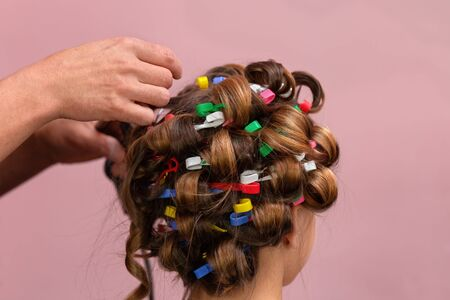 Hairdresser making Hair roller for a kid. Flesh-coloured background Zdjęcie Seryjne