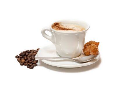 Cup of coffee with milk and cinnamon, a sweet to accompany it. Roasted coffee beans Stockfoto