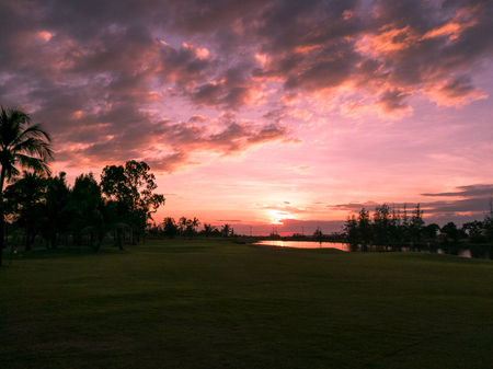 golf course scene during sunset with water reflection
