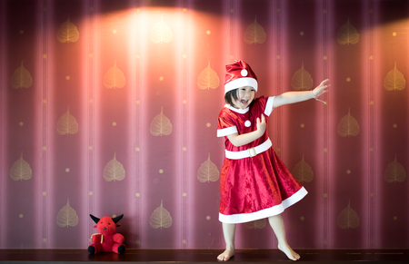 Santa kid dances with happiness on christmas celebration beside red doll