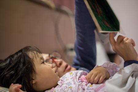 Asian Kid listening fairy tale from mother before sleeping Foto de archivo