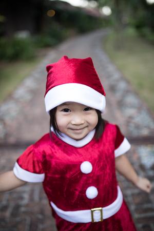Asian santa kid smiles under Santa dress on christmas eve 스톡 콘텐츠