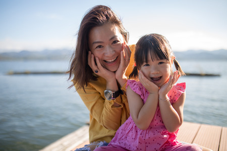 Asian mother daughter pose smile faces together, family relationship Stock Photo